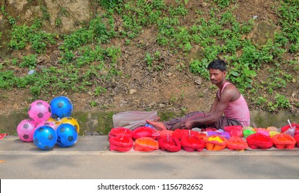 Guwahati, India - June 23, 2018: A man selling red sindoor or vermilion, and colorful balls sitting by the road.