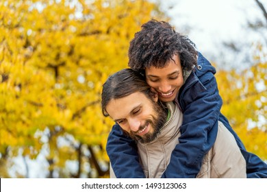 guy with an african  girl in love hugging  in autumn park walk at sunset