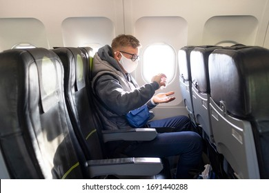 Guy im Flugzeug, junger Mann in Brillen, medizinische Schutzbrille auf seinem Gesicht sitzend im Flugzeug mit Sanitizer für die Desinfektion der Hände gegen Coronavirus, Virus Bakterien. Pandemie-Kokosnuss-19