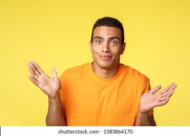 Guy apologizes, cant help, dont have anything to offer. Awkward cute caucasian masculine man spread hands sideways, shrugging and smiling as cannot say, puzzled answer, yellow background