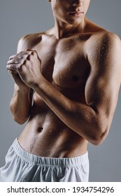 guy with athletic body on gray background gesturing with hands bodybuilder