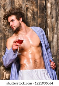 Guy attractive relaxing with alcohol drink. Bachelor enjoy wine after bath. Man sexy chest wet skin after bath hold wineglass. Macho tousled hair degustate luxury wine. Drink wine and relax.