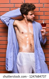 Guy attractive relaxing with alcohol drink. Bachelor enjoy wine. Macho tousled hair degustate luxury wine. Drink wine and relax. Erotic and desire concept. Man sexy chest sweaty skin hold wineglass.