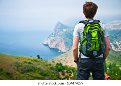 a guy with a backpack on the nature of the mountains is worth looking at a view