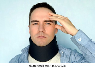 A guy with a bad neck in a black neck collar to stabilize the cervical vertebrae. A man with a neck injury on a blue background. spinal fracture. headache.