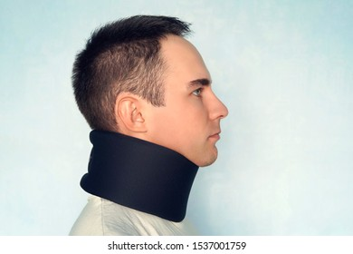 A guy with a bad neck in a black neck collar to stabilize the cervical vertebrae. A man with a neck injury on a blue background. spinal fracture. Young man wearing neck collar on blue background