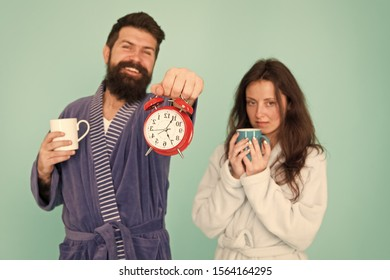 Guy in bath clothes hold tea coffee. Breakfast concept. Every morning begins with coffee. Couple in bathrobes with mugs. Its coffee time. Man with beard and sleepy woman enjoy morning coffee or tea.