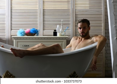 Guy in bathroom with toiletries and stairs on background. Man with beard and surprised face. Macho sitting naked in bathtub. Relaxation and erotica concept.