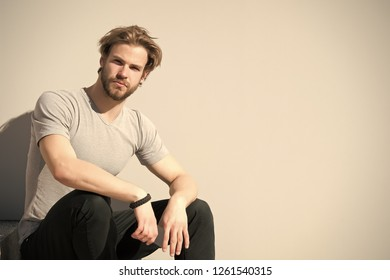 Guy with beard and blond hair in casual tshirt. Macho hold smartphone on sunny outdoor. Bearded man with mobile phone on grey wall. New technology and modern life, copy space.