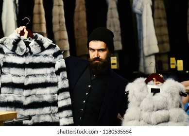 Guy with beard chooses furry coats. Elegance and glamour concept. Man with serious face holds furry coats with clothes rack on background. Shop assistant with hat and expensive overcoats.