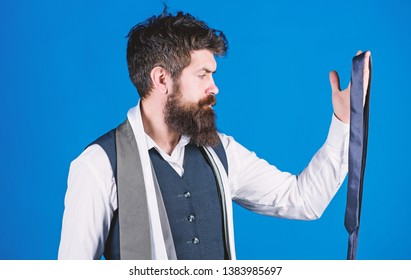 Guy with beard choosing necktie. Gentlemens guide. How to choose right tie. Classic style. How to match necktie with shirt and suit. Man bearded hipster hold few neckties on blue background.