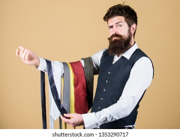 Guy with beard choosing necktie. Perfect necktie. Select tie that has colors of your suit and shirt as well as at least one other color to provide an accent. Man bearded hipster hold few neckties.