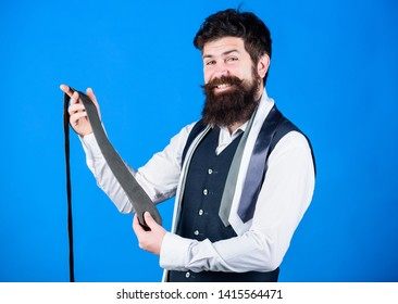 Guy with beard choosing necktie. Perfect necktie. For formal occasions choose solid colored tie that is darker than your shirt. Match colors. Man bearded hipster hold few neckties on blue background.