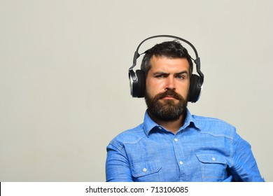 Guy with beard and concerned face listens to music. Man wears big earphones on grey background, copy space. Macho with beard enjoys music, copy space. Music and leisure concept.