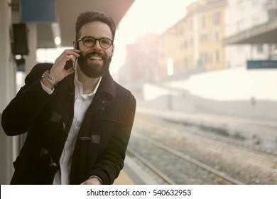 Guy with beard feeling cheerful while talking on the phone, waiting for the train