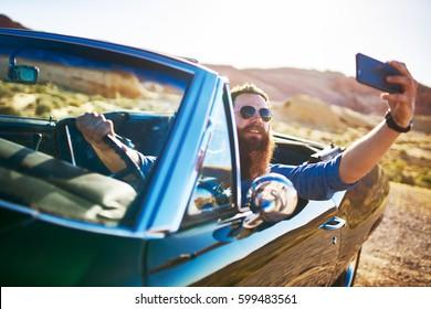 guy with beard taking selfie in vintage car