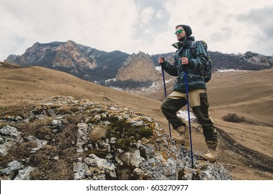 A guy with a beard and wearing sunglasses in a membrane jacket, hat, with a backpack and sticks for Nordic walking, a traveler standing and looking at the mountains