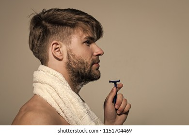 Guy with bearded face profile with razor and towel on grey background. Morning routine concept. Beauty, barber, hairdresser salon. Grooming, hygiene, skin care, copy space