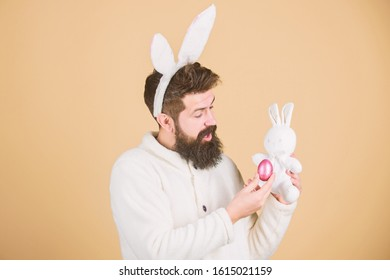 Guy bearded hipster cheerful bunny with long white ears. Easter rabbit. Man wearing rabbit suit play with toy. Funny bunny man soft ears. Easter activities concept. Still childish. Celebrate Easter.