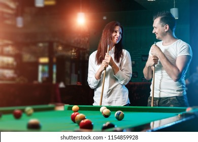 A guy and a beautiful girl are playing billiards, a guy is teaching a girl to play billiards. Dark background. Pleasant pastime, family rest, entertainment, holiday.