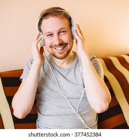 A guy with a beautiful smile listening to music on headphones and sitting on the couch at home, square image