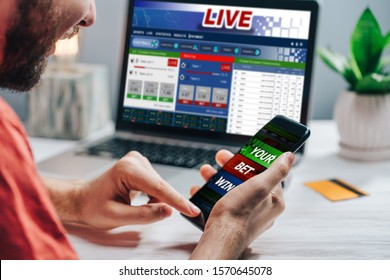 Guy being happy winning a bet in online sport gambling application on his mobile phone.