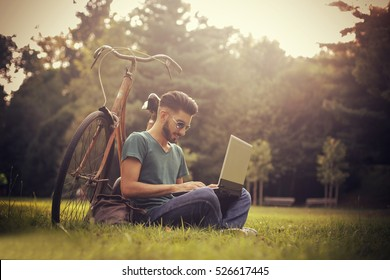 Guy being outside with his laptop and bike