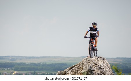 the guy with the bike on top of the mountain