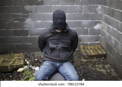 Guy in black jacket and jeans sitting in chair tied up.