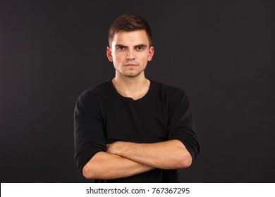 A guy in black jacket poses with his arms crossed over his chest against a black background. Indoors.