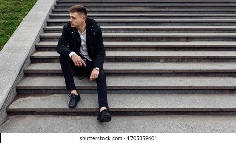 Guy in black jacket sitting on stairs while looking away outdoors. Copy space. Lifestyle concept