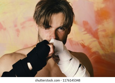 Guy with black kimono belt and bandage on arms. Healthy lifestyle and jujitsu concept. Man with confident face and naked torso on colorful background. Boxer or karate fighter practices martial arts.
