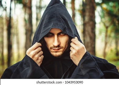 the guy in the black robe, standing in the dusk in the woods