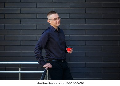 The guy in the black shirt is drinking coffee from a red paper cup.