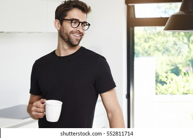 Guy in black t-shirt with coffee in kitchen