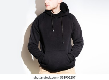 the guy in the Blank black hoodie, sweatshirt, stand, smiling on a white background, mock up, free space, logo, template for print,  design