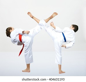 A guy with a blue belt and a girl with a red belt makes a high kick