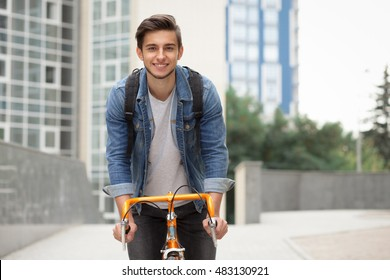 A guy in a blue denim jacket on orange bicycle. The man on the background of the city with a backpack on a bike smiling at the camera