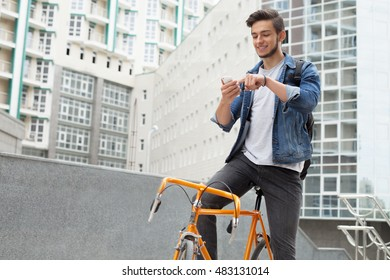 The guy in a blue denim jacket standing on city background. a young man near orange bicycle. Smiling student with bag looking at phone