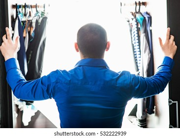 The guy in the blue shirt opened the closet with clothes