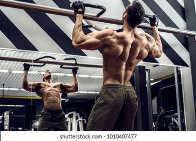 guy bodybuilder execute exercise pulling up on horizontal bar in gym, horizontal photo