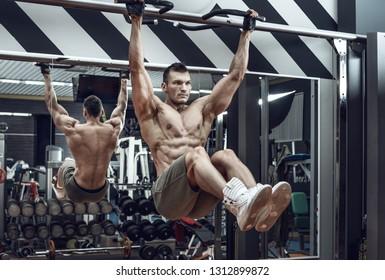 guy bodybuilder , perform exercise do chin-ups, horizontal bar in gym