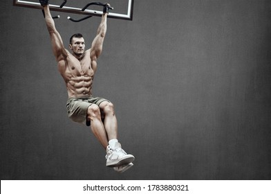 Guy bodybuilder perform exercise do chin-ups, horizontal bar on grey wall background with empty space for text. Gym concept