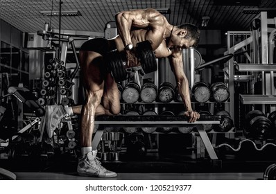 guy bodybuilder, perform exercise with dumbbell on broadest muscle of a back, in dark gym