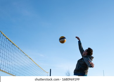 guy bounces a bouncing ball playing beach volleyball near the net. in cold weather in clothes.