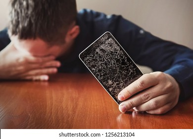 Guy with bristles, is showing his hand on a smartphone. Broken screen of modern frameless phone. guy crying with his eyes closed and hands in his face.