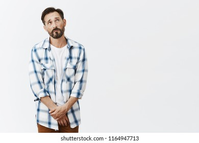 Guy cannot please wife like used to. Portrait of miserable and gloomy european male model with beard and moustache, frowning and gazing with sad look up, holding palms together on pants