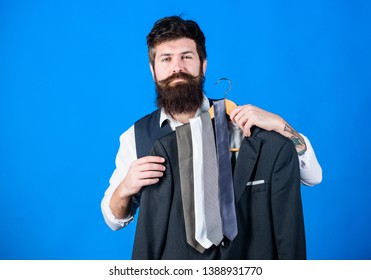 Guy choosing necktie. Perfect necktie. Shopping concept. Shop assistant or personal stylist service. Stylist advice. Matching necktie with outfit. Man bearded hipster hold neckties and formal suit.