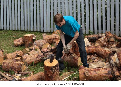 Guy chopping wood with a pine CRIN and a sledgehammer. At the farmhouse.