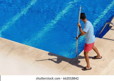 A guy cleaning the swimming pool ground with a telescopic vacuum head. Summer pool maintenance service